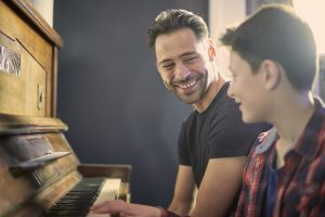man and son at a piano